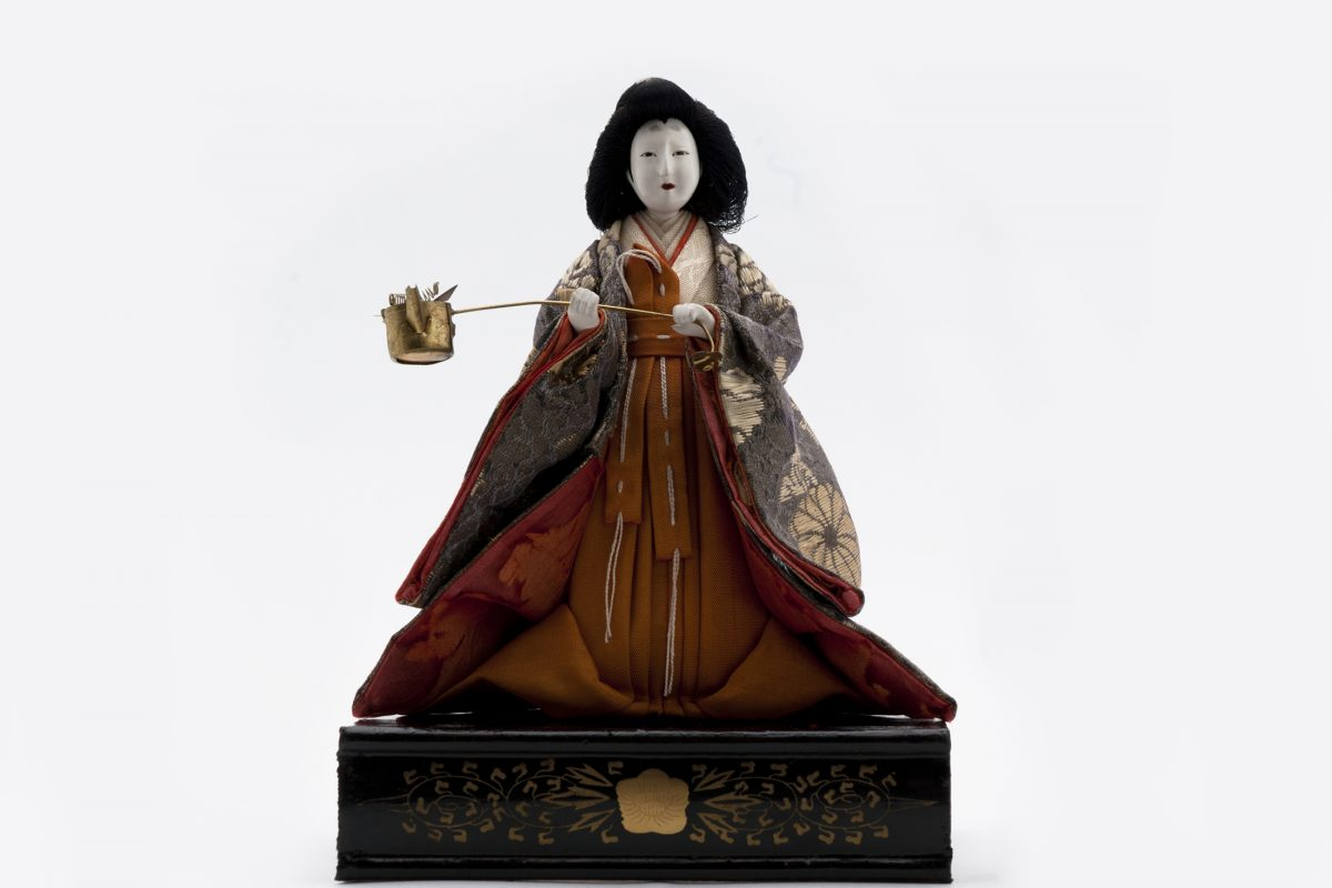 Figure of doll with painted white face and long wide dress. The doll is holding a small pot on a stick and the doll is stood on a black box with gold detailing.
