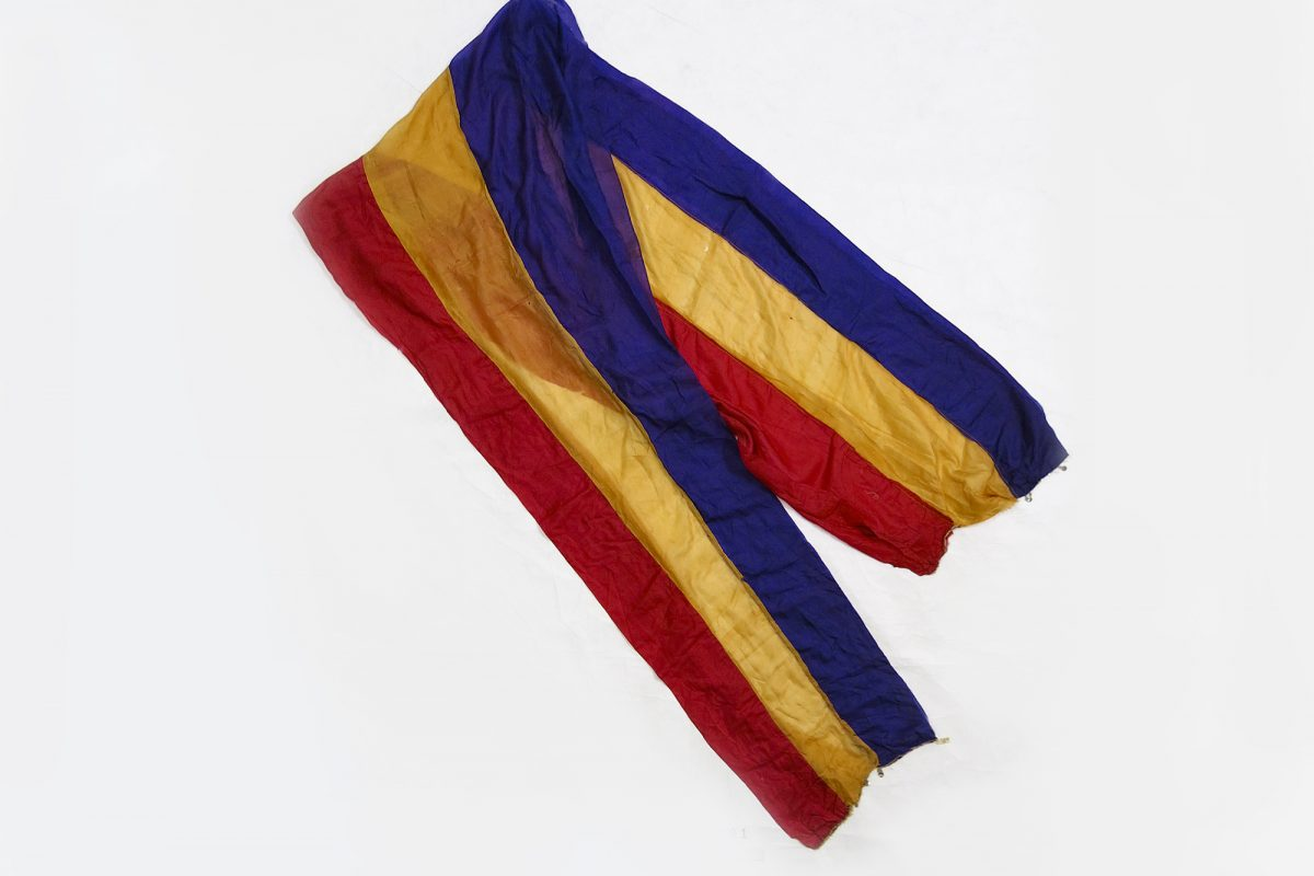 A piece of light fabric with three stripes of colours, red, yellow and blue.