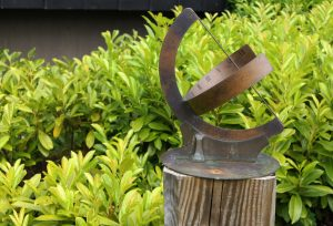 A metal curved sundial in a garden