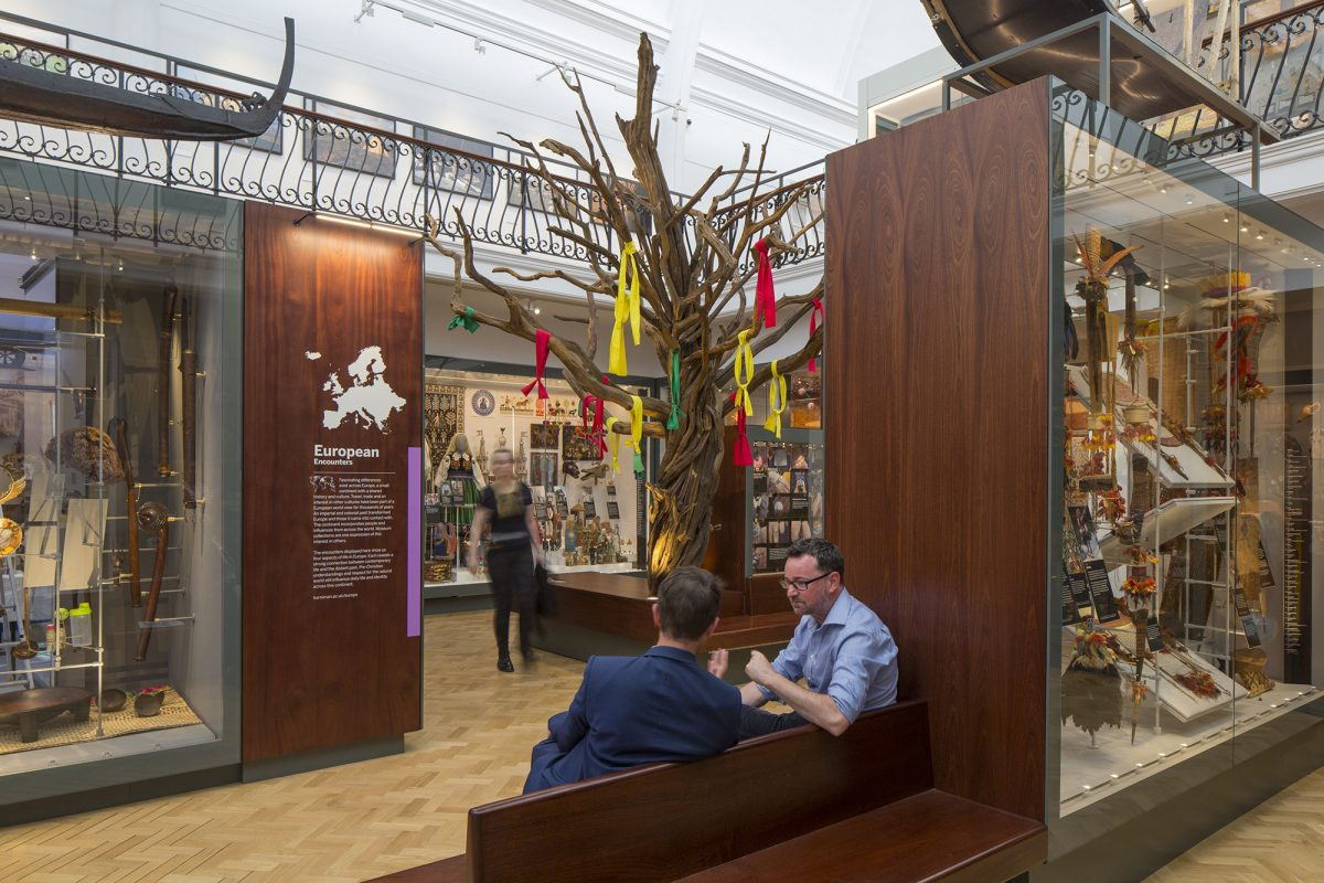 A tree with strips of fabric hanging from the branches sits in a gallery. Two men sit on a bench in the foreground and a woman is walking past the tree looking into display cases.
