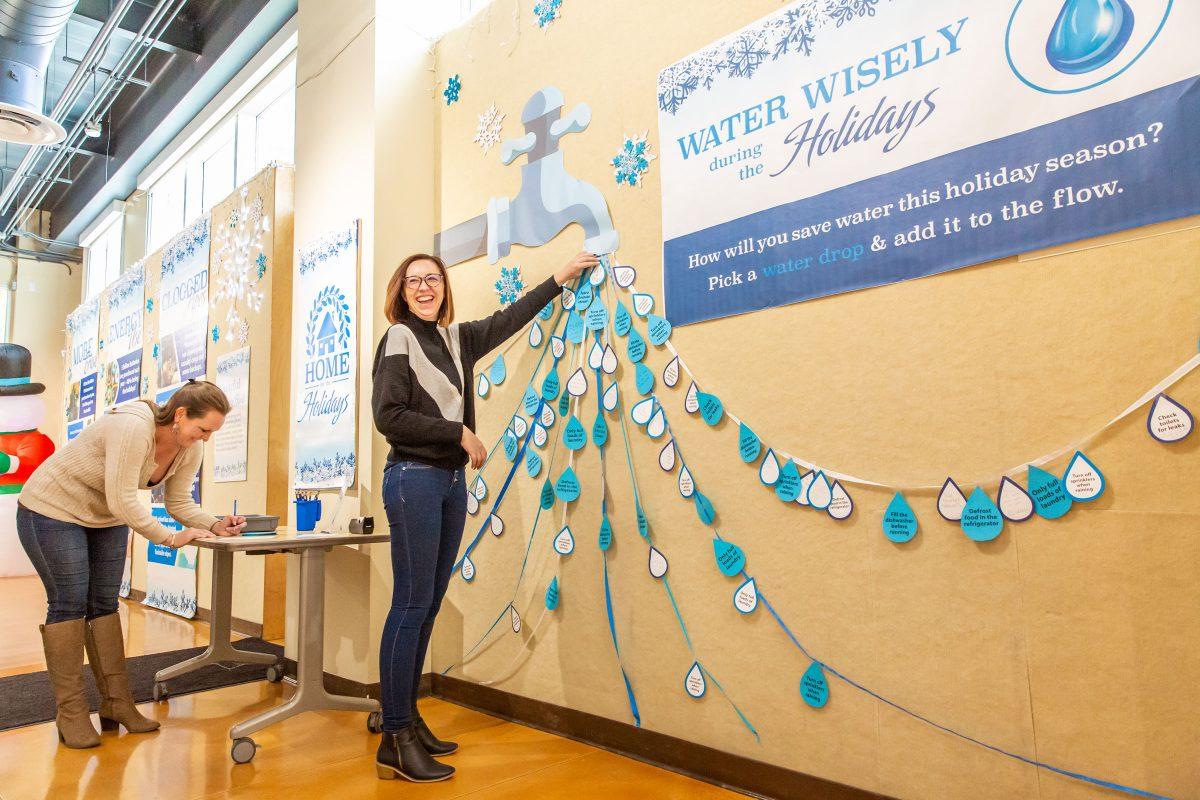 Visitors pin water drops to a wall