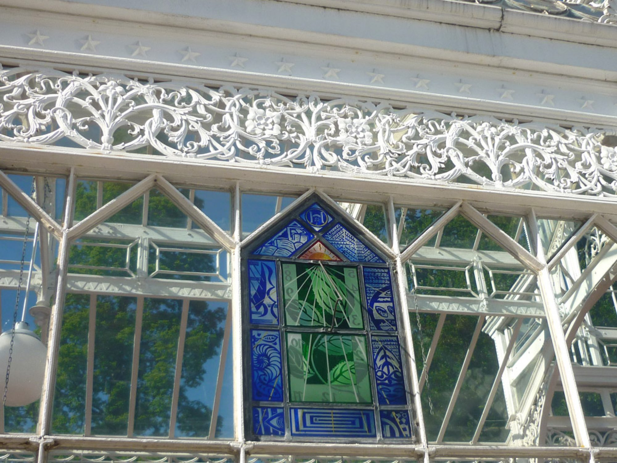 A glass panel in a conservatory with a sundial on it