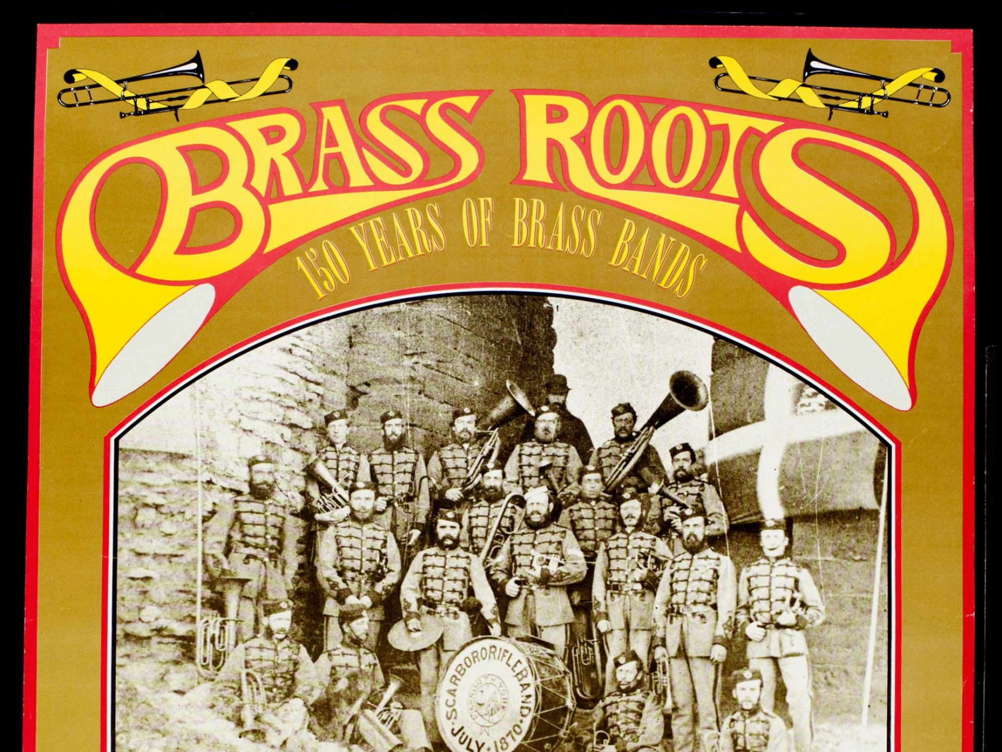 A poster about brass music with the words brass roots in yellow, made to look like brass instruments. There are black and white photographs of bands beneath