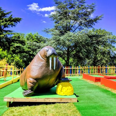 A model of a walrus standing on a yellow golf ball is in a garden golf course on a sunny day