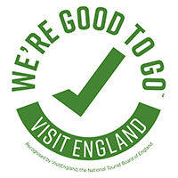 A green circular logo with We're good to go written on the top half, a tick in the middle, and the words visit England written on the bottom of the circule
