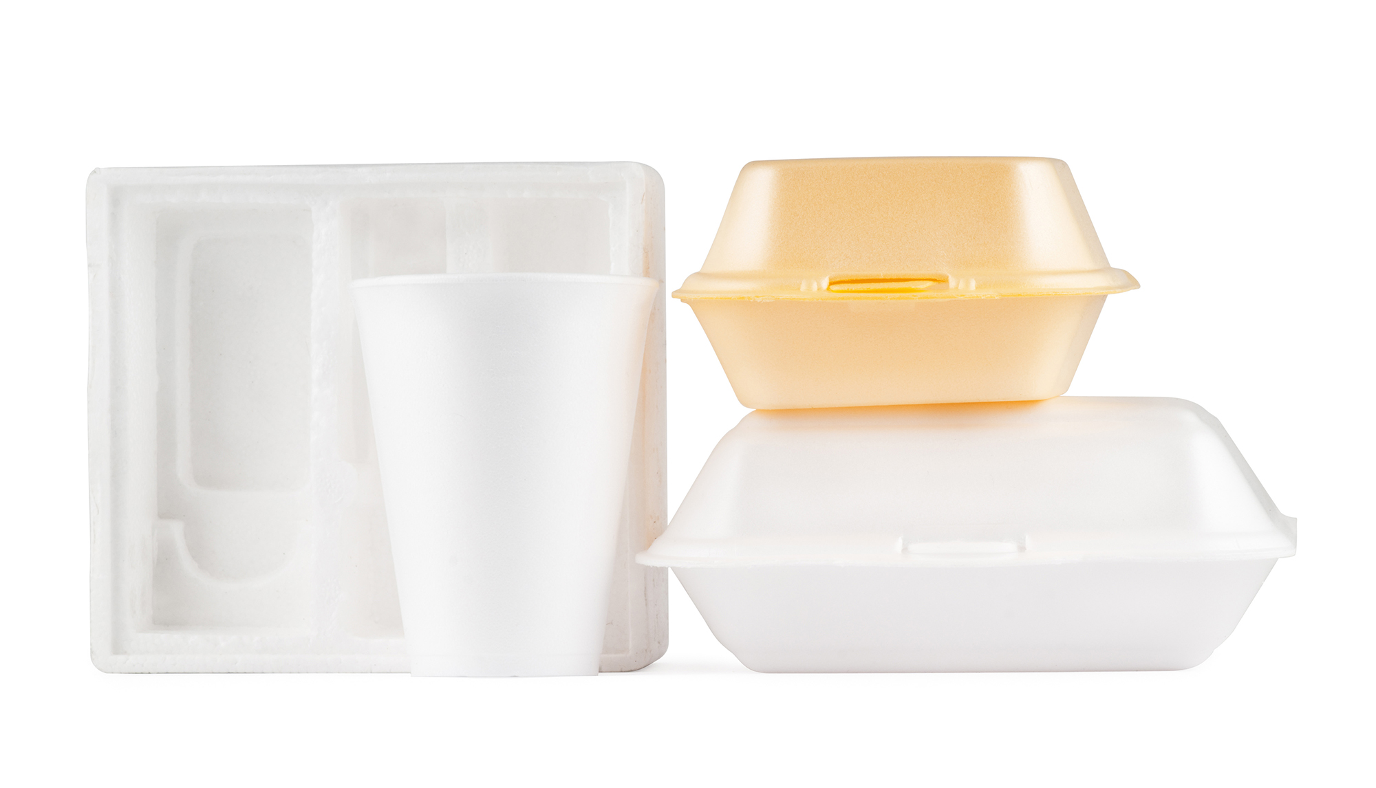 A selection of polystyrene including electronic packaging, cups, fast food containers and food trays, isolated on a pure white background