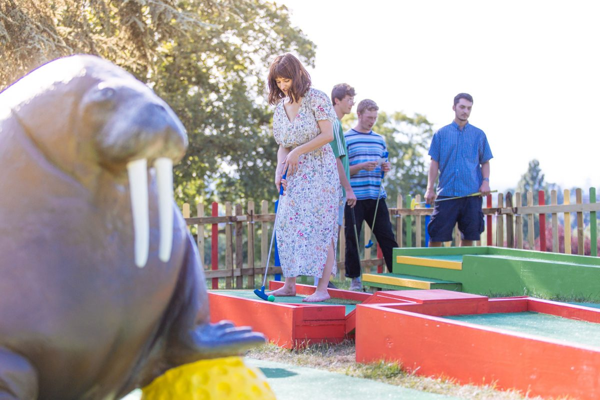 A group of young adults plays on a golf course next to a large walrus statue