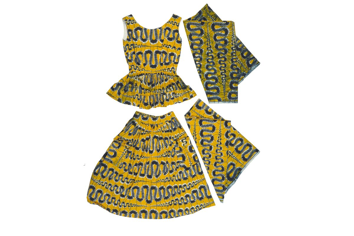 An outfit made from yellow and black printed fabric laid flat on a white background. There are four pieces: a sleeveless top, a skirt and two side swatches of fabric.