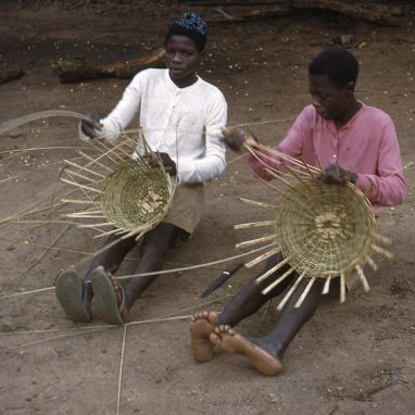 Two women sitting on bare ground weaving baskets on their laps.
