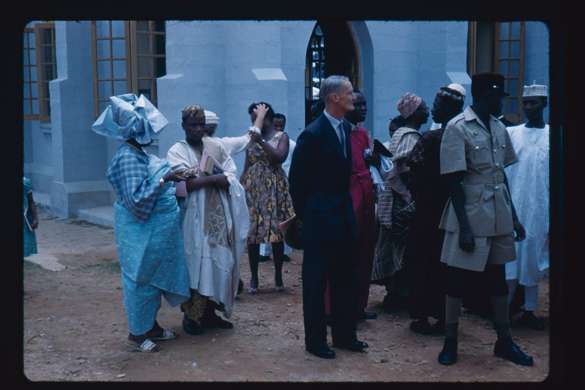 A old colour photo of a formal or celebratory occasion. Two people to the left are in blue and white clothes. A man to the centre is in a suit and to his right is a man in a khaki uniform. Behind him are a group of people wearing robes. Behind the people in the foreground is a woman in a sun dress who is holding a second woman's arm, who is in a white dress. The woman in the white dress is reaching for her and looking away from her at the same time