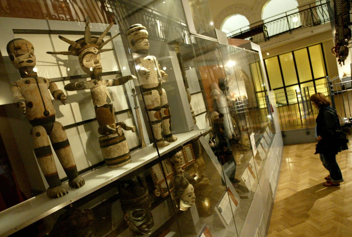 A photograph of a gallery taken at a slightly skewed angle. There is a case in front with wooden figures, some painted white and a woman looking into the case. The light is low and the floor is wooden.