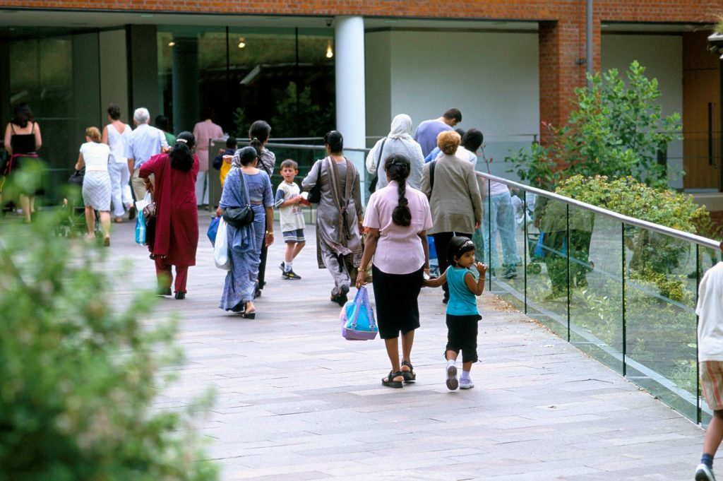 A group of adults and children walking along a path to a building, which is the Horniman. The path is edged with glass fence and there are plants to either side.
