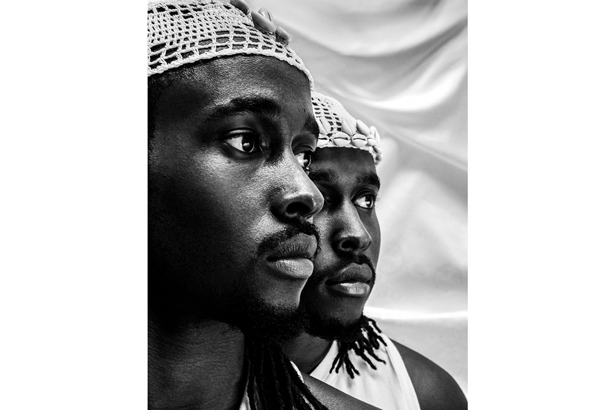 Black and white photo of two black men, faces half seen