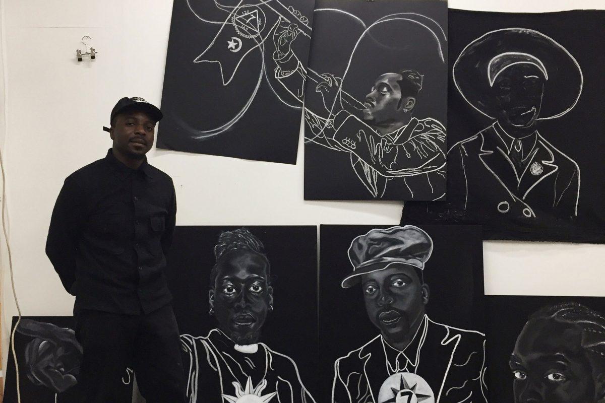 Hamed Maiye standing next to artwork