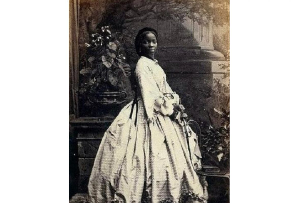 Black and white image of woman with long hair in period dress.