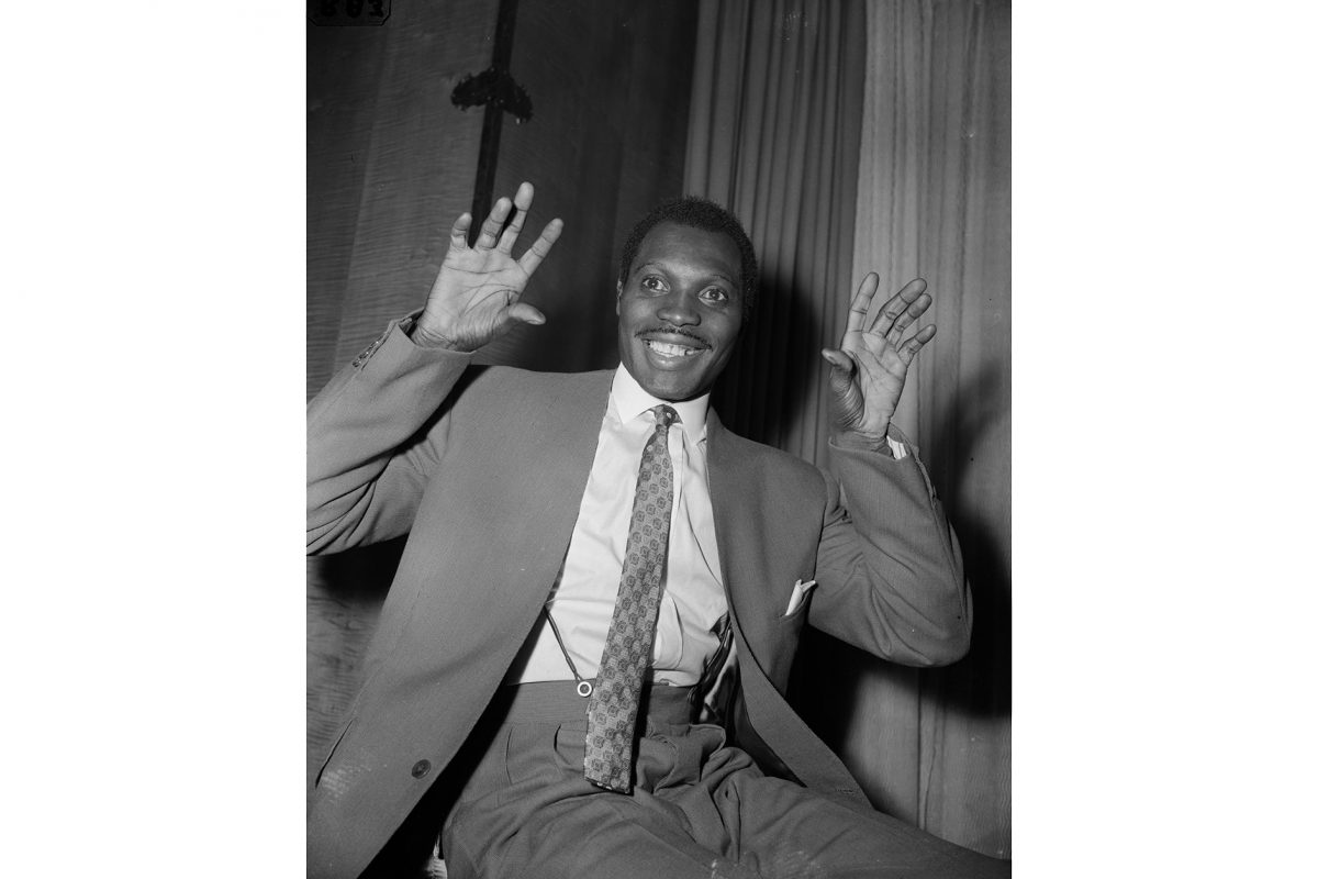 Image of man sitting down with hands raised up