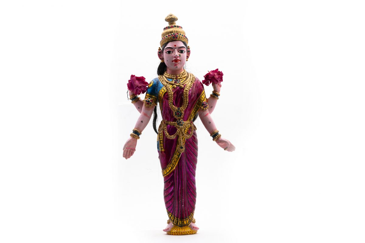Polychrome wooden figure depicting Lakshmi wearing a purple-pink sari and holding two pink paper flowers