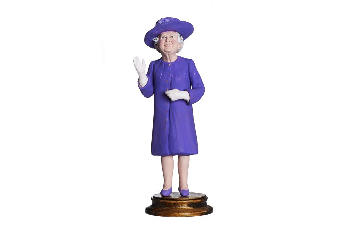 Figure of the Queen wearing purple hat, shoes and skirt suit. Figure mounted on a wooden stand.