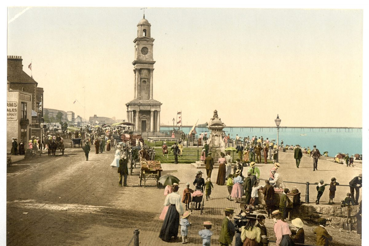 A colourised postcard of a victorian sea front with clock tower
