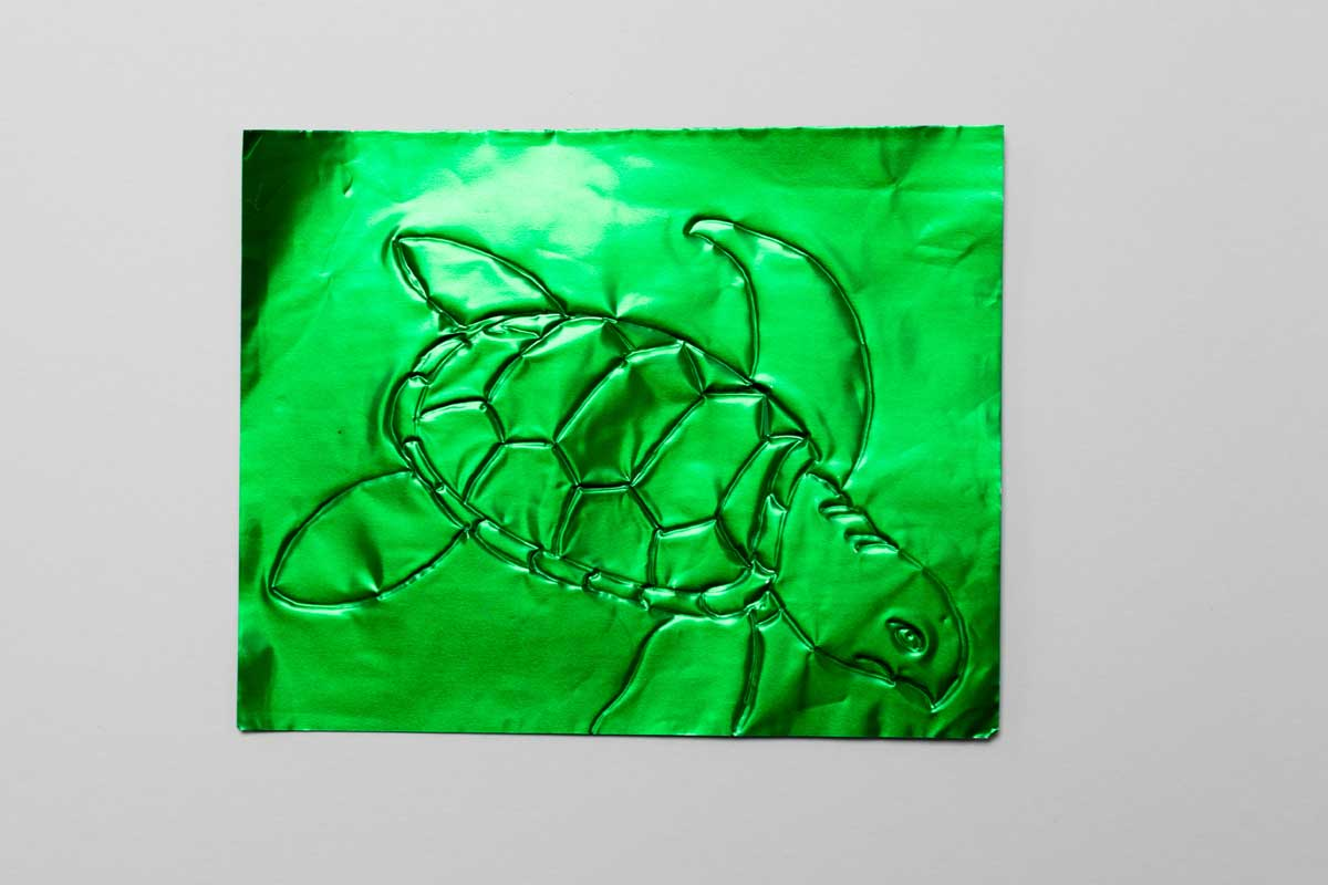The outline of a turtle on green shiny paper
